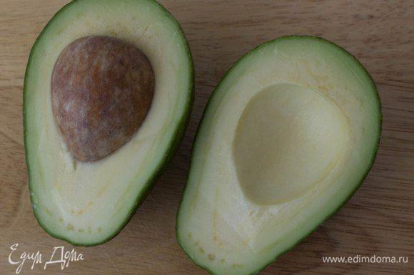 Авокадо разрезать на две части, удалить косточку, очистить и нарезать тонкими ломтиками.