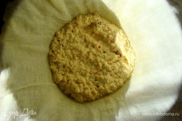Дуршлаг зафиксировать в кастрюле, сверху распределить марлю в два слоя и постепенно выложить сырную массу.