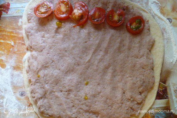 На тонко раскатанное тесто выложить тонким слоем фарш. На один край выложить порезанный помидор.