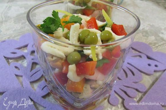 Разложить по высоким бокалам коктейль, кубики перцев, горошек, лимонную цедру и зелень.