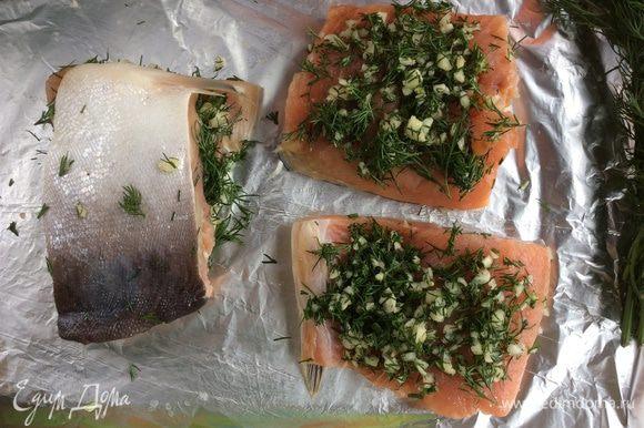 Возьмите лист фольги, смажьте совсем немного растительным маслом, положите на неё рыбу кожей вниз, сверху выложите зелень с чесноком и накройте второй половинкой филе.