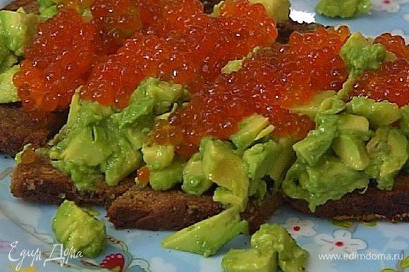 На хлеб поместить авокадо, сверху выложить икру и нарезать бутерброд на небольшие порционные кусочки.
