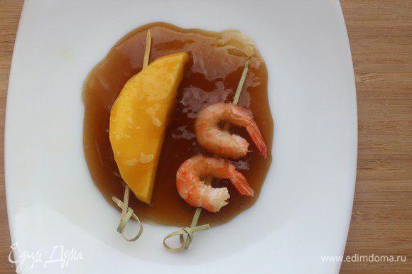 Обмакнуть шпажки с креветками и манго в глазурь и быстро обжарить на гриле до появления карамельных подпалин. Посыпать розовым перцем и подавать.