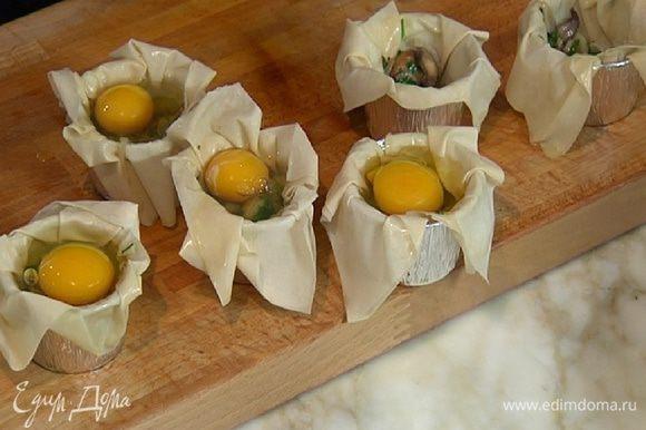 Выложить в формы с тестом грибную начинку и разбить по одному яйцу.