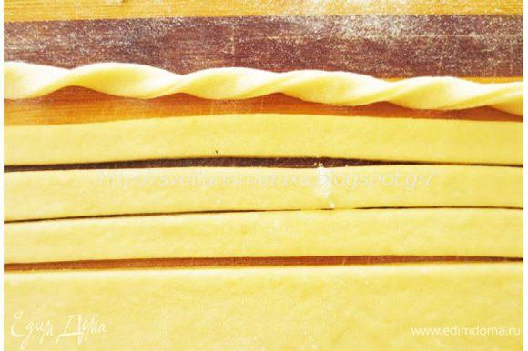 Из второй части теста раскатываем овальную или прямоугольную лепешку и ножом для пиццы разрезаем на длинные полоски, примерно 1 см шириной. Каждую полоску скручиваем в спиральку.