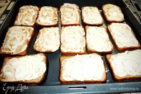 Нарезаем лук полукольцами и раскладываем на хлеб.