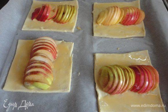 Слоеное тесто (предварительно размороженное) слегка раскатать, чтобы получилось 8 прямоугольников размером на 6 см больше диаметра яблока. У меня были некрупные яблочки. Противень застелить бумагой и выложить тесто. Посередине каждого кусочка выложить «дорожку» из яблок (по 2 половинки одного яблока), края смазать смесью желтка и молока.