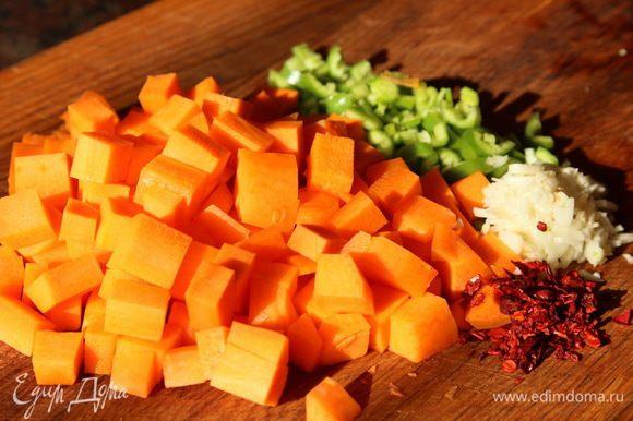 Морковь нарезаем кубиком, горький перец и чеснок рубим и отправляем к мясу. Добавляем лепестки перца чили или просто сушеный красный острый перец, тимьян.