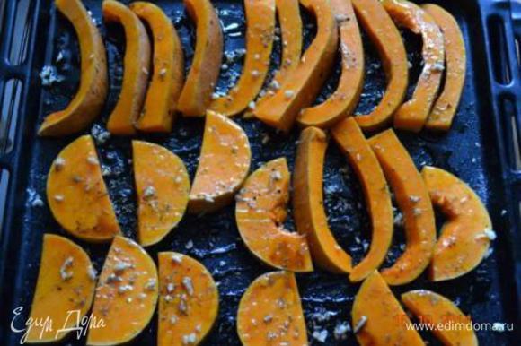 Выложить на противень. Порубить мелко чеснок и посыпать сверху тыкву, посолить, поперчить, полить медом, бальзамико и оливковым маслом, посыпать сухим или свежим тимьяном. Запекать в заранее разогретой духовке до 180 С 35-40 минут.