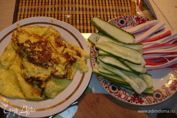 Порезать крабовые палочки соломкой, огурцы тонкими дольками, сделать омлет из яиц и немного молока.