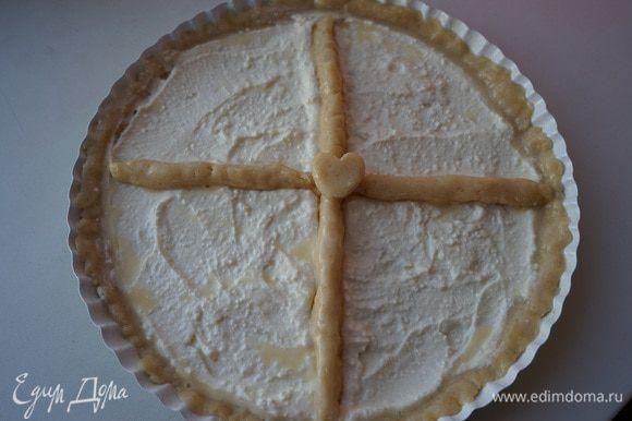Раскатать тесто по размеру формы, сделать бортики. Получившуюся массу выложить на тесто. Из оставленного теста сделать перегородки. 1/3 яйца обмазываем края и перегородки пирога.