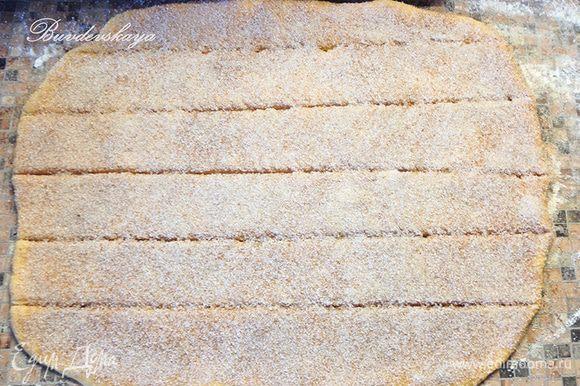 Вымесите тесто 2 минуты и раскатайте его в прямоугольник. Смажьте его растопленным маслом и посыпьте специями. Разрежьте тесто на 6 полос (примерно 8-9 см шириной).