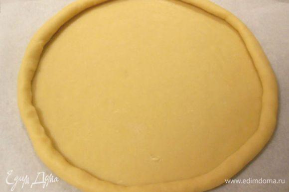 Пальцами плотно скатывать тесто по кругу от краёв к центру, пока диаметр не станет 25 см и сделать бортик 2 см высотой.
