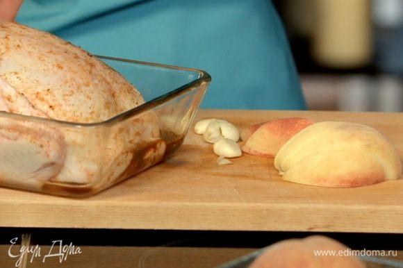 Нафаршировать курицу чесноком и персиками, уложить в смазанную маслом форму и запекать при температуре 180С около часа - до образования румяной корочки.