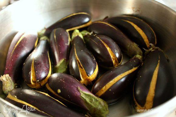 В большой сковороде нагрейте 2 ст.л. масла, выложите баклажаны в один слой и обжаривайте на маленьком огне под крышкой. Для равномерного приготовления периодически переворачивайте их и готовьте до мягкости.