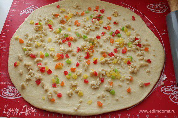 Раскатайте тесто в прямоугольник. Выложите цукаты и нарезанный небольшими кусочками марципан.