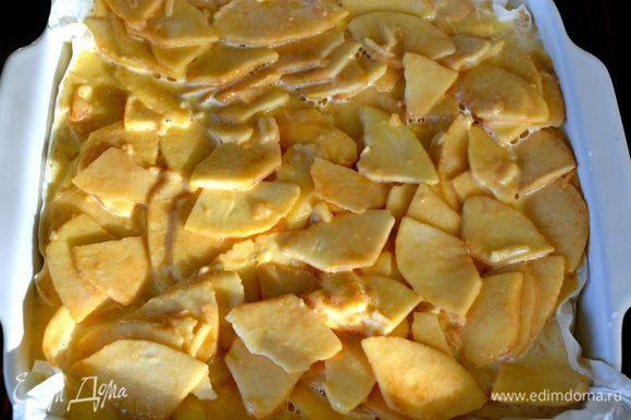 Нам потребуется огнеупорная форма для выпечки 25х25 см или 30х23 см. Пекарскую бумагу смочить в воде и как следует отжать, стряхнуть лишние капли воды и выложить бумагой форму для выпечки. Выложить яблоки и разровнять.