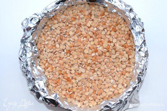 Сверху положить фольгу, насыпать горох или керамические шарики (для того, чтобы основа не потеряла форму при выпечке). Отправить в заранее прогретую духовку и выпекать при 180 градусах минут 10-15 минут.