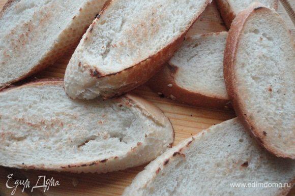 Багет нарезать ломтиками и слегка обжарить на сухой сковороде. Ломтик чеснока надрезать и натереть им каждый ломтик багета.