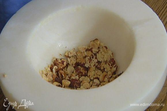 Обжаренные орехи измельчить в ступке так, чтобы остались крупные кусочки.