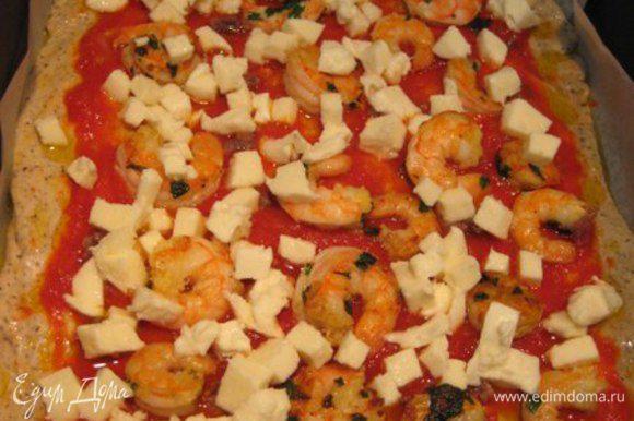 Анчоусы измельчить, моцареллу порезать кубиками. Выложить на пиццу анчоусы, креветки, моцареллу и запекать 20 минут. Через 20 минут посыпать тертым пармезаном и запекать еще 2-3 минуты.
