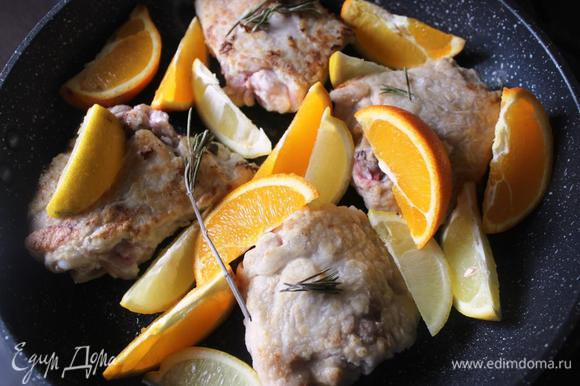 Апельсин и лимон нарезать на 8 частей каждый. Выложить их на сковороду к курице, добавить веточку розмарина по желанию, накрыть крышкой и потушить еще минут 15.