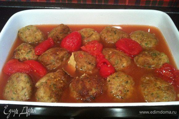 Переложите фрикадельки в форму для запекания, добавьте консервированные томаты, оставшееся оливковое масло, лавровые листья и щепотку соли. Запекайте в предварительно нагретой до 190 градусов духовке 30 минут. Каждые 10 минут поливайте фрикадельки томатным соусом.