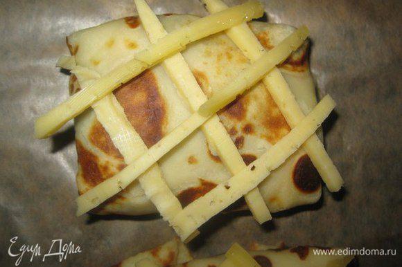 Блины с начинкой выкладываем на противень, застеленный пекарской бумагой. Наверх выкладываем узенькие полосочки сыра, клеточками.