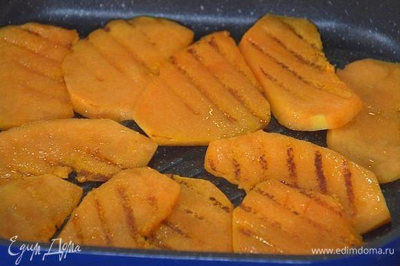 Разогреть сковороду-гриль и обжарить ломтики тыквы с двух сторон практически до готовности.