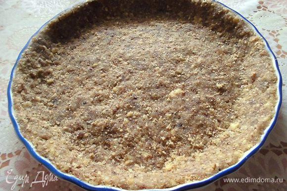 Изюм и грецкие орехи прокрутить через мясорубку. Взять форму (у меня керамическая, диаметром 21,5 см) и выложить туда основу, сделать бортики. Убрать в холодильник, пока буде готовиться начинка.
