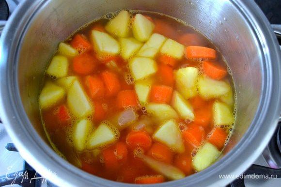 Залить все горячим (!) овощным бульоном, посолить по вкусу и варить на среднем огне 30 минут или до готовности моркови.