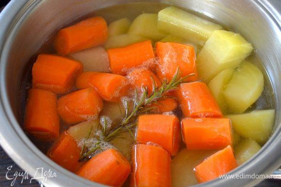 Очистить морковь и картофель. Одну морковку отложить в сторону. Остальные овощи нарезать кусочками, выложить в кастрюлю и залить холодной водой. Поставить на огонь, довести до кипения и варить 30 минут (я добавила веточку розмарина).