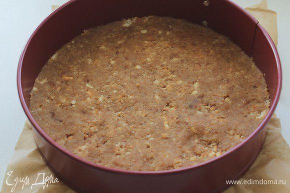 Разъемную форму диаметром 24 см застелить бумагой для выпечки, и равномерно распределить песочную крошку. Утрамбовать и отправить в холодильник на 45-50 мин.