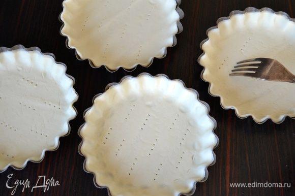 Формочки для тарталеток слегка смазать оливковым маслом и выложить в них тесто. Наколоть вилкой, чтобы тесто не вздулось при выпечке.