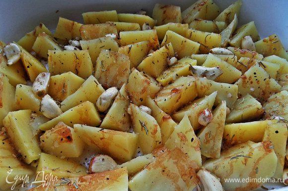 Сливаем картошку, распределяем в один слой в керамической форме, сверху разбрасываем чеснок и поливаем заправкой.