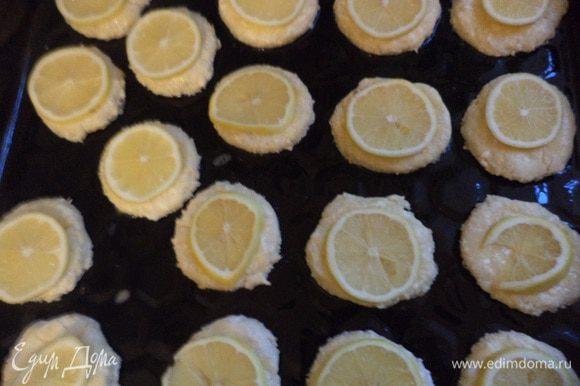 Лимоны тщательно вымыть, вытереть насухо полотенцем и нарезать на очень тонкие дольки. Лимонные дольки выложить сверху на печенье, посыпать крупным сахаром. Выпекать при температуре 180 градусов 12 - 15 минут.