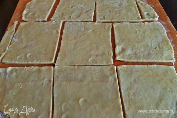 Вынимаем тесто, отрезаем примерно треть (остальное убираем в холодильник) и раскатываем тонко в квадрат или прямоугольник. Нарезать на квадратики. Дополнительную муку я указала для присыпки на доску.