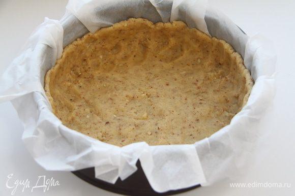 Разъёмную форму диаметром 20 см застелить бумагой для выпечки, распределить тесто по дну и бортикам. Убрать в морозилку на 20 минут.