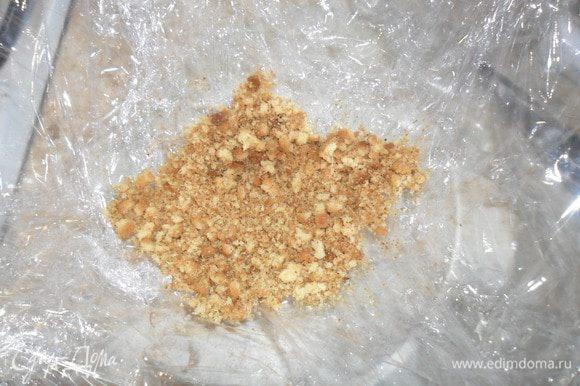 Круглую форму (салатник) застелить пленкой и на дно всыпать немного крошки.