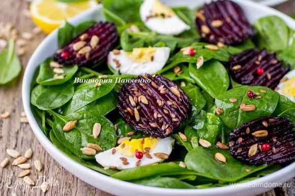 Выложить на плоскую тарелку помытый и обсушенный шпинат, яйца нарезать кольцами или дольками вдоль, выложить поверх шпината, разложить запеченную свеклу, посыпать льняными и подсолнечными семечками. Сбрызнуть оливковым маслом и подавать к столу.
