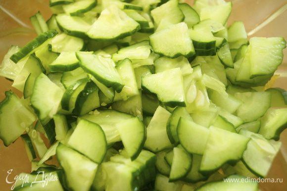У перцев убрать лишнюю мякоть и сердцевину с семенами. Мякоть перцев нарезать небольшими кусочками. Огурцы нарезать тонкими дольками и выложить в салатник вместе с мякотью перцев.