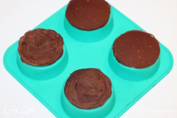 Берем силиконовые формочки, переворачиваем их как на фото и смазываем верх (чайной ложкой) растопленным шоколадом. У меня получилось 12 кружочков (Ф ~6 см), т. е. на четыре больших пирожных по три кружка. Вместо силиконовых формочек, можно взять силиконовый коврик или пергаментную бумагу (смазать маслом). Кружочки отправляем в холодильник до застывания шоколада. Застывшие кружочки слегка поддеваем ножиком и они легко снимаются с формочки.