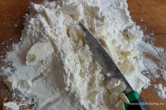 Муку высыпаем на доску, на муку выкладываем холодное сливочное масло и рубим ножом, пока оно не превратится в крошку.