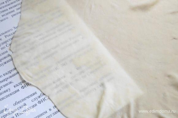 Затем растягиваем пласт теста в разные стороны на тыльной стороне рук. Тянем до того пока тесто не станет просвечивать, но главное следим за тем, чтобы оно не порвалось.