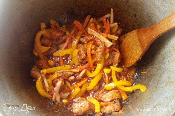 Затем перец, немного обжарить, не переставая мешать.