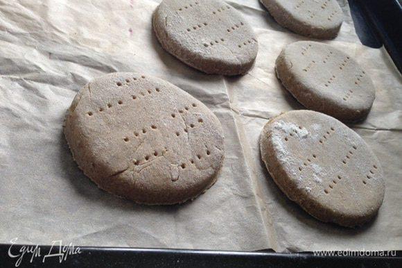 Выложить тесто на хорошо присыпанную мукой рабочую поверхность, также присыпать сверху и раскатать пласт толщиной 1.5 см. Вырезать кружочки, переложить их на противень, застеленный бумагой для выпечки, и отправить в духовку на 25-30 минут при температуре 180 градусов.