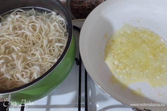 Лапшу опустить в кипящую воду и варить 5-7 минут. На сливочном масле обжарить чеснок с имбирем, помешивая, 2 минуты.