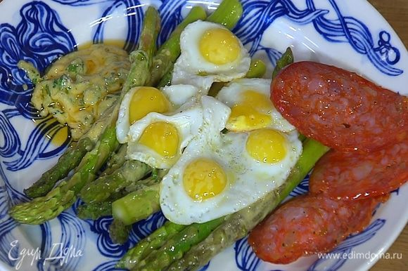 Выложить спаржу вместе с соусом на тарелку, сверху поместить перепелиные яйца и кусочки колбасы.