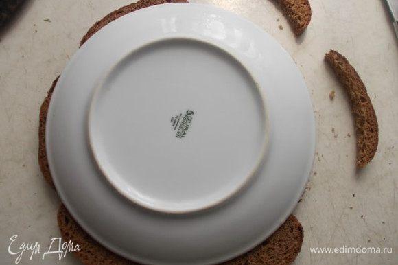 Берем кусочки ржаного хлеба, у меня уже порезанные. Если у вас целая булка, значит порежьте сами. Кладем сверху тарелку и вырезаем по кругу, чтобы тортик у нас получился нужной формы.