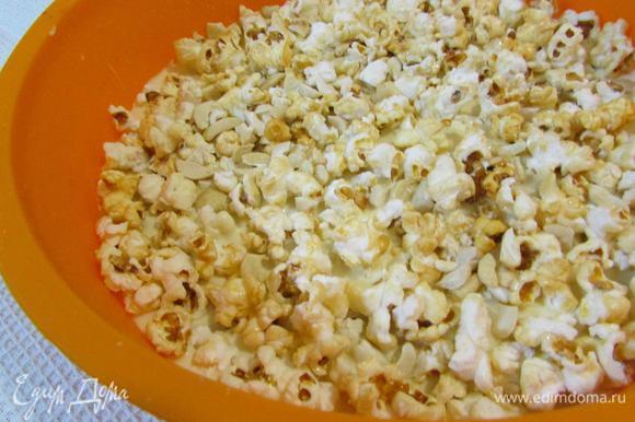 Сразу же выложить на него попкорн и кешью. Слегка придавить, чтобы шоколад и ореховая смесь соединились.